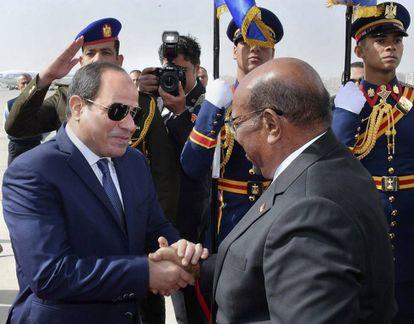 El presidente sudanés, Omar al Bashir, es recibido por el mandatario egipcio, Abdelfatá al Sisi, este domingo en el aeropuerto de El Cairo.