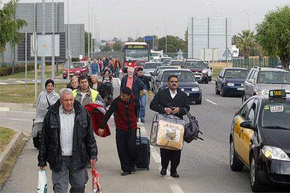 Varios viajeros dirigiéndose a pie hacia el aeropuerto debido al colapso circulatorio.