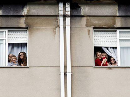 Miembros de la familia Dorrio Cuadrado saludan desde las ventanas de su piso en Ferrol.