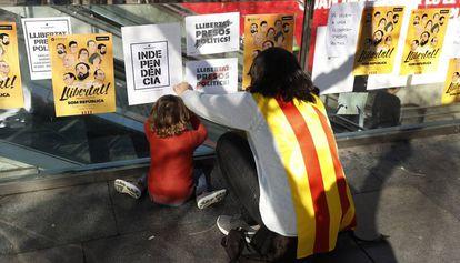 Una mujer y un niño pegan carteles por la independencia catalana el 5 de noviembre.