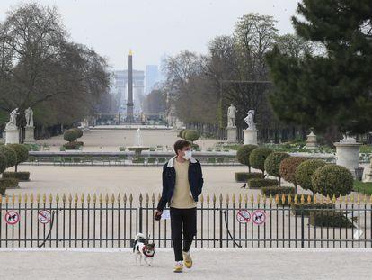 Un hombre pasea al perro en el jardín de las Tullerías, en París, el día que entra en vigor el confinamiento obligatorio.