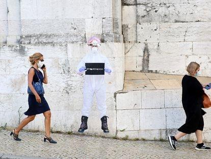 """Mujeres con mascarilla pasean por Lisboa ante un cartel que dice """"quédense en casa"""""""