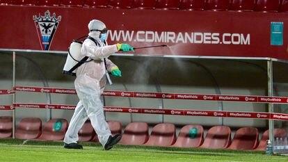 Un operario desinfecta los banquillos del estadio Municipal de Anduva.