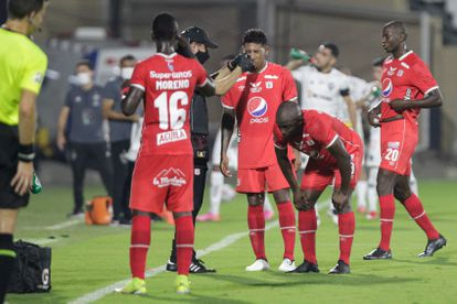 An assistant helps the América de Cali players affected by tear gas during their Copa Libertadores match against Atlético Mineiro, at the Romelio Martínez stadium in Barranquilla.