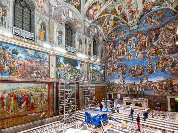 Varios trabajadores colocan los tapices de Rafael en la Capilla Sixtina, en el Vaticano.
