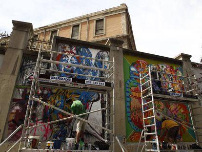 Dos artistas gráficos pintan los muros de La Tabacalera.