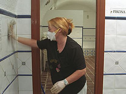 Una empleada limpia los baños del balneario de Cortes y  Graena.