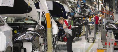Una operaria trabaja en una fábrica de automóviles.