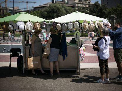 Varias personas compran sombreros para protegerse de la calor en plaza Catalunya de Barcelona.