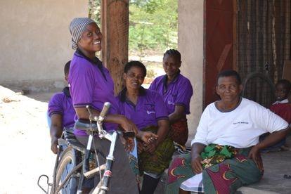 Louise, manager en Msitu Wa Tembo de la tienda de alquiler de bicicletas, descansa apoyada en una bici frente a otras mujeres de la comunidad.