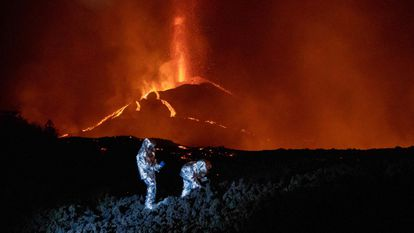 """In this handout photograph taken and released by the Spanish Military Emergency Unit (UME) on October 16, 2021, members of the GIETMA (Technological and Environmental Emergencies Intervention Group) of the UME monitor the evolution of a new lava flow, following the eruption of the Cumbre Vieja volcano, on the Canary island of La Palma. - There is no prospect of the volcanic eruption in Spain's Canary Islands ending """"in the short or medium term"""", experts said on October 13, 2021 after three-and-a-half weeks of activity. (Photo by Luismi Ortiz / UME / AFP) / RESTRICTED TO EDITORIAL USE - MANDATORY CREDIT """"AFP PHOTO / LUISMI ORTIZ  / SPANISH MILITARY UNIT (UME) """" - NO MARKETING - NO ADVERTISING CAMPAIGNS - DISTRIBUTED AS A SERVICE TO CLIENTS"""