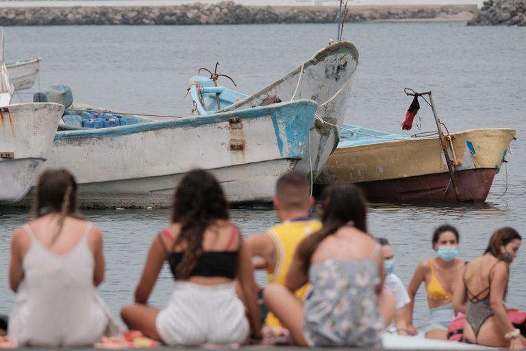Bañistas frente a los cayucos amontonados en el muelle de Arguineguín, en Gran Canaria, donde han llegado a pernoctar bajo carpas más de 400 inmigrantes.