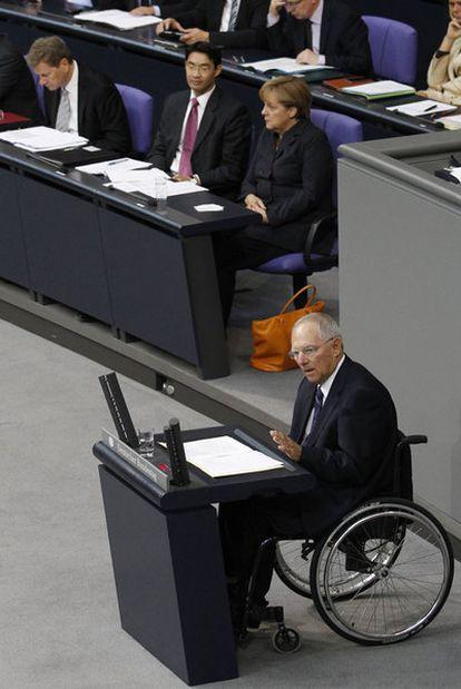 Schäuble con Merkel al fondo, ayer en el Bundestag.