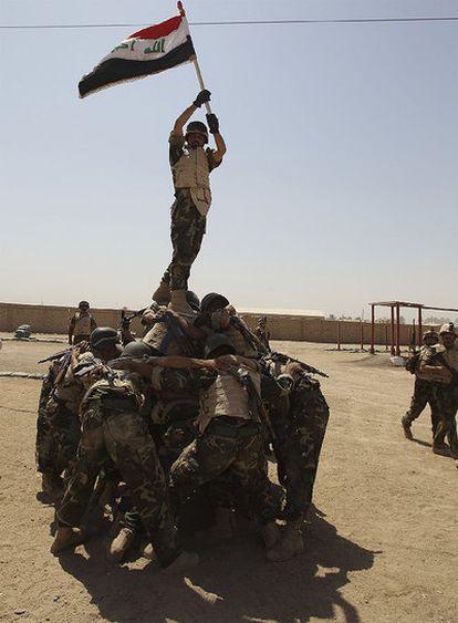 Soldados iraquíes sostienen una bandera de su país para los fotógrafos tras una sesión de entrenamiento en una base al sur de Bagdad.