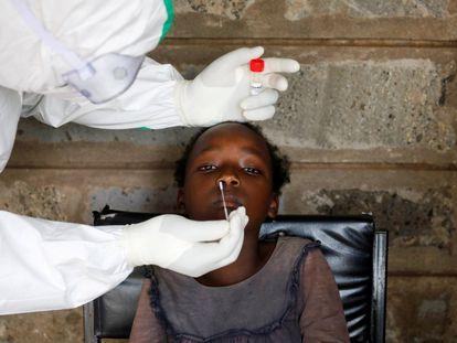 Un sanitario realiza una PCR a una niña durante una prueba masiva en un barrio marginal de Kibera en Nairobi (Kenia).
