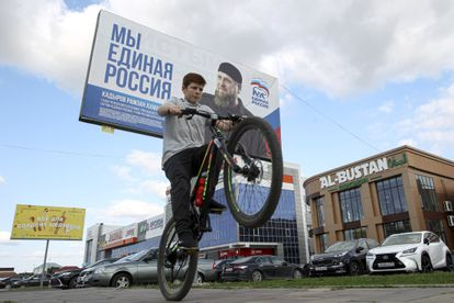 Un niño pasa en bicicleta ante un cartel electoral de Rusia Unida con un retrato de líder checheno Ramán Kadírov, este martes en Grozni.