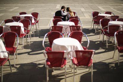 Dos turistas se sientan en una terraza vacía en la plaza de San Marcos en Venecia.