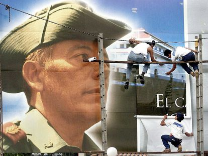 Trabajadores municipales de ciudad de Panamá despliegan un póster gigante con el retrato del militar Omar Torrijos, anterior líder de Panamá como preparación de la celebración de la entrega del control total del canal de Panamá por parte de Estados Unidos al país centroamericano en diciembre de 1999. / EPA
