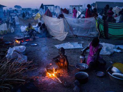 Un niño se calienta cerca de una hoguera mientras su madre prepara la cena en el campo de desplazados de Bentiu, en Sudán del Sur.