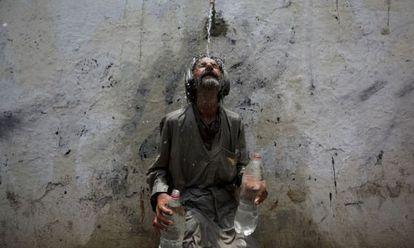 Un hombre se refresca en una fuente de Karachi (Pakistán) para paliar los efectos de las altas temperaturas.
