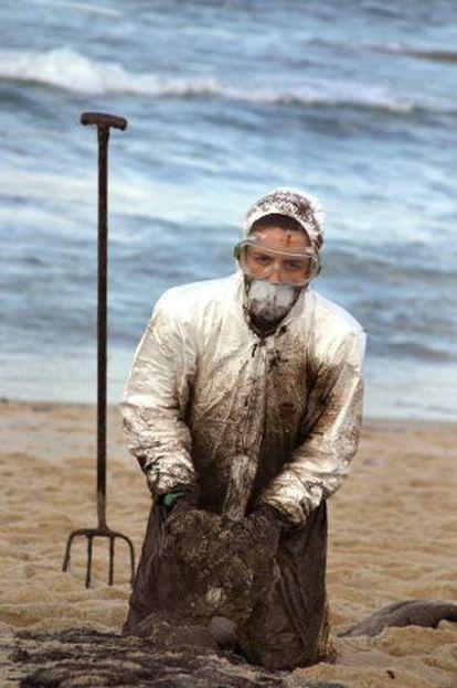 Una voluntaria recoge chapapote en Lira (A Coruña) en 2002.