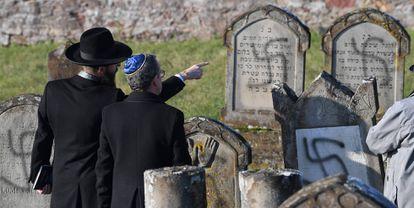 Dos hombres señalan las tumbas destrozadas en diciembre de 2019 en el cementerio judío Westhoffen cerca de Estrasburgo (Francia).