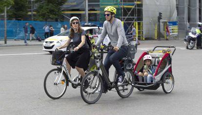 Dos ciclistas pedalean llevando a varios niños durante la manifestación.