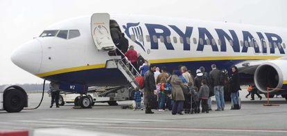 Decenas de pasajeros suben a un avión de la compañía aérea Ryanair.
