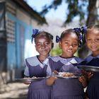 Tres niñas haitianas posan con sus platos de bulgur en su escuela. El Programa Mundial de Alimentos sirve hasta 250.000 menús a diario en las escuelas del país.