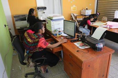 Una mujer trabaja con su bebé en la espalda en Cajolá, Guatemala.