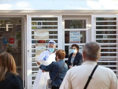 Una sanitaria sale a atender a las numerosas personas que hacen cola en el Centro de Salud Vicálvaro-Artilleros en el distrito de Vicálvaro, en Madrid el 28 de septiembre.