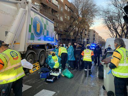 Samur y policía atienden a la mujer junto al camión de la basura.