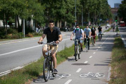 Varias personas se mueven en bicicleta por un carril bici de Barcelona.