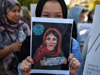 Una joven sostiene una pancarta durante una manifestación de miembros de la comunidad afgana frente a la embajada de Estados Unidos en Atenas después de que los talibanes llegaran al poder en Afganistán el 28 de agosto de 2021.