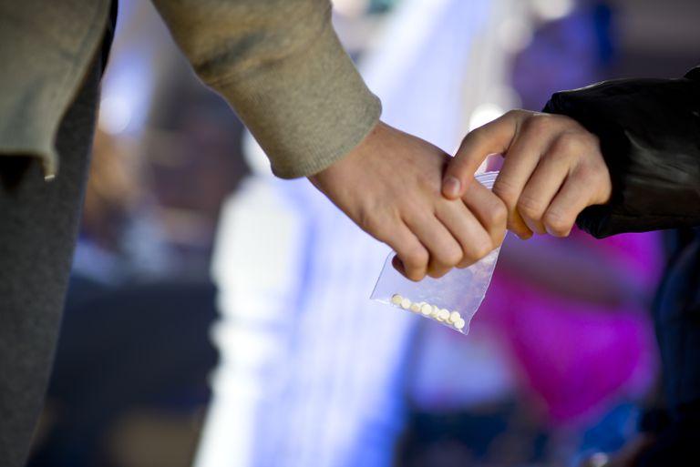 Una persona entrega a otra una bolsa con pastillas de MDMA.