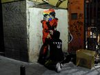 """Street artist TVBoy pastes a new artwork entitled """"Tokyo Loves Nairobi"""" depicting a rainbow-coloured heart along with two characters from the """"Casa de Papel"""" show locked in a kiss in a street in Madrid late on September 12, 2020. (Photo by OSCAR DEL POZO / AFP) / RESTRICTED TO EDITORIAL USE - MANDATORY MENTION OF THE ARTIST UPON PUBLICATION - TO ILLUSTRATE THE EVENT AS SPECIFIED IN THE CAPTION"""