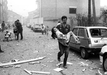 Un guardia civil lleva en brazos a una niña a la que le falta un pie, en el atentado contra la casa cuartel de la Guardia Civil en Vic (Barcelona), el 29 de mayo de 1991.