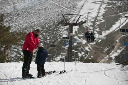 Juan Yánez ajusta el abrigo a su hijo Rodrigo, de seis años, al que ha llevado por primera vez a esquiar este viernes.