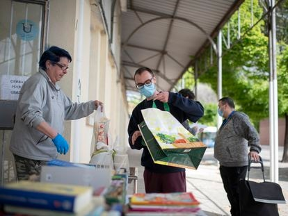 Varias familias esperan en la cola del centro de voluntario de caritas en Orcasur para recoger alimentos.