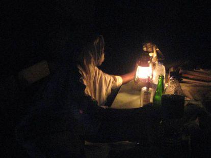 Un matrona hace guardia alumbrada solo con una lámpara de keroseno.