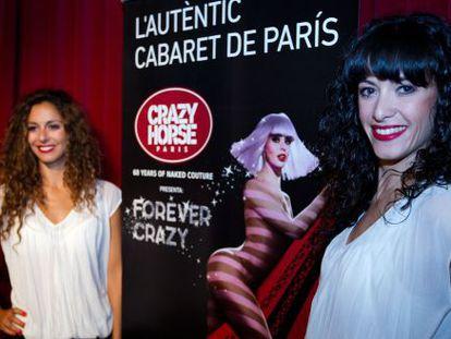 Dos de las bailarinas del cabaré parisino Crazy Horse, ayer en Barcelona junto al cartel anunciador del espectáculo.