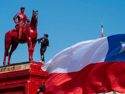 Un manifestante pinta el monumento al General Baquedano durante una protesta contra el gobierno de Chile en Santiago.