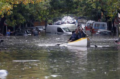 Habitantes de Buenos Aires se desplazan en canoa por las calles, el martes tras las lluvias.