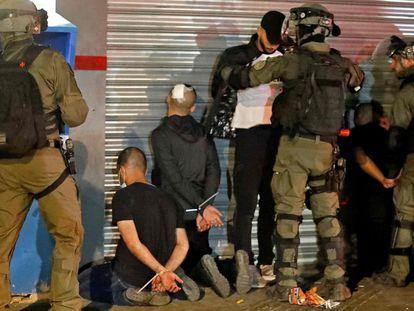 Fuerzas de seguridad israelíes cachean a un grupo de árabes israelíes detenidos en Lod, el jueves.