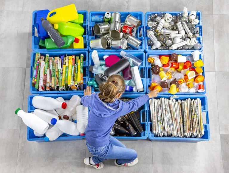 Una niña separa los residuos para luego reciclarlos.