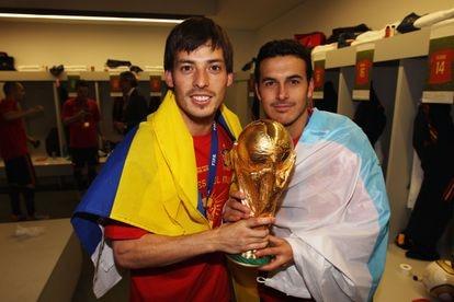 Silva, con la bandera de Las Palmas, y Pedro con la de Tenerife, sostienen la Copa del Mundo conseguida por España en Sudáfrica 2010.