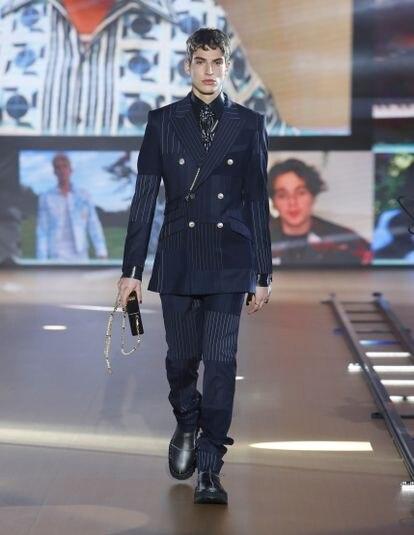 Un traje de chaqueta cruzada con 'patchwork' de tejidos lisos y de raya diplomática abre el desfile otoño/invierno 2021 de Dolce&Gabbana.