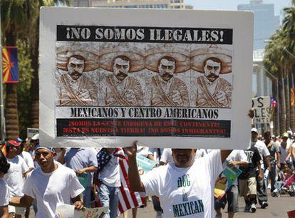 Un hispano sostiene una pancarta en contra de la nueva ley antiinmigración durante una protesta en Phoenix, Arizona.