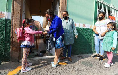 Una maestra toma la temperatura a una estudiante, durante el regreso a clases en León, Guanajuato, el pasado 11 de mayo.