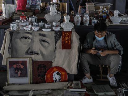 Un hombre con mascarilla vende recuerdos de la era de Mao en un mercado de Pekín